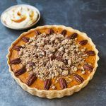 pumpkin pie with nuts on top and cream on the side