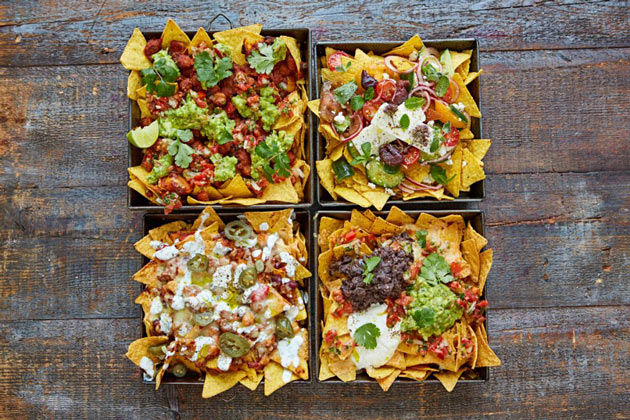 4 dishes of nachos with different toppings on top