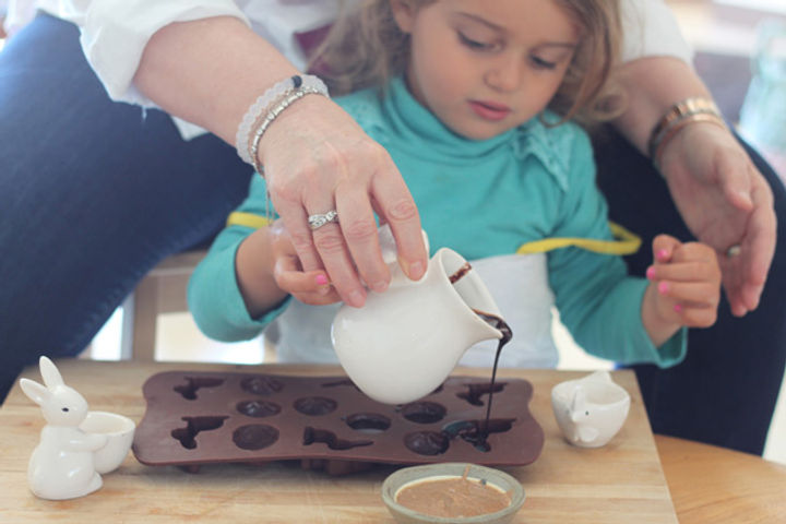 A mother helping her daughter pour chocolate into a bunny shaped mould