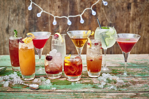 an array of cocktails with ice and fruit garnishes