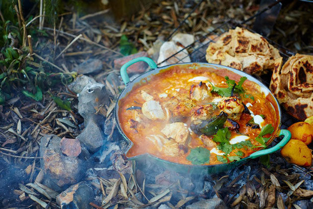 indian curry recipe cooked outside on stove with bread