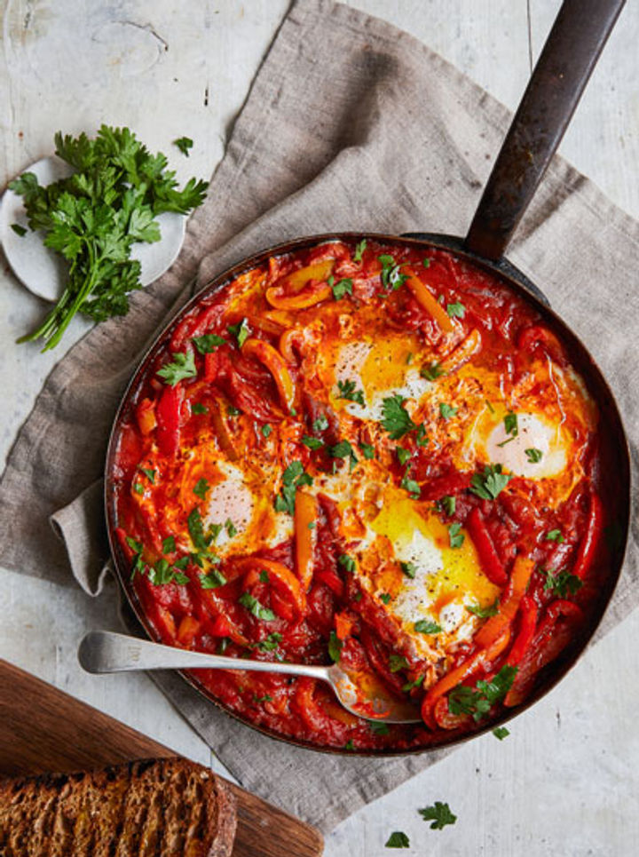shakshuka egg recipe in a pan with tomato and herbs scattered on top