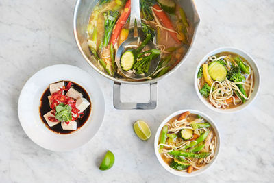 Pot and bowls of vegetarian noodle soup