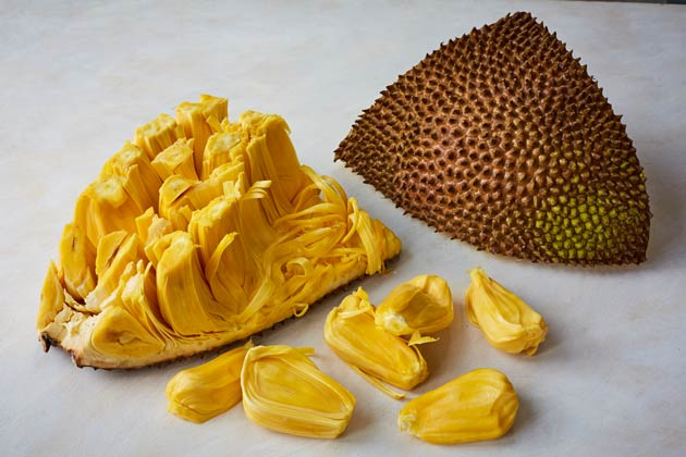 A jackfruit cut in half, the inside showing the 'meat of the fruit' and half showing the outside