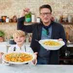 Buddy holding a large plate full of pasta next to Jamie holding another bowl punching the air with his fist