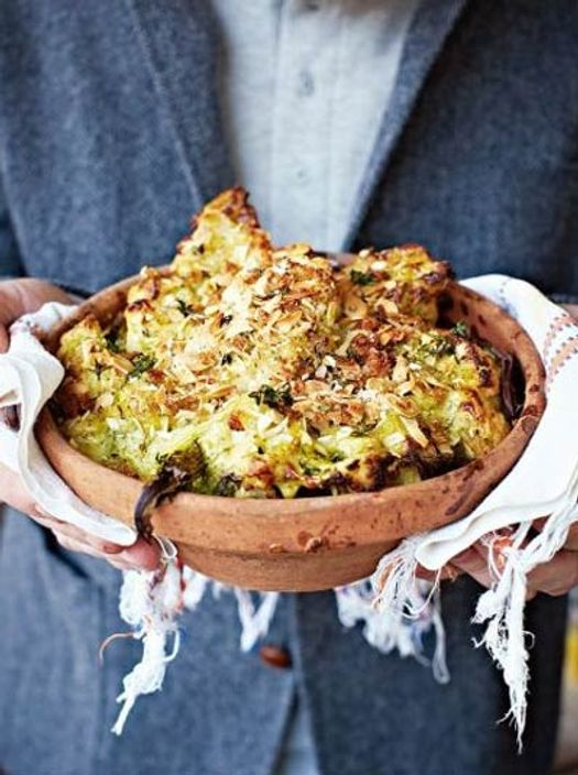 person holding a terracotta pot full over baked broccoli and cauliflower cheese