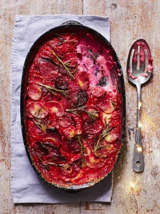 Black baking tray filled with beetroot gratin with a serving spoon on the side