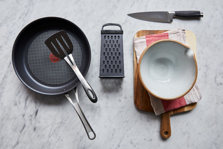 Equipment for making hash browns: frying pan, spatula, grater, knife, bowl, chopping board and teatowel