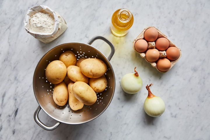 Ingredients for making hash browns: potatoes, eggs, onions, flour, oil