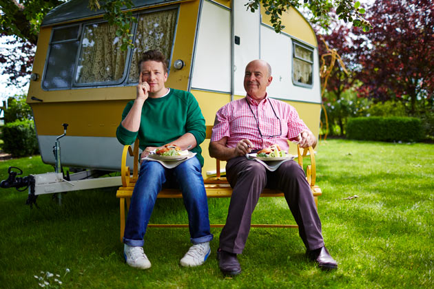 Jamie and his dad sitting in front of a caravan
