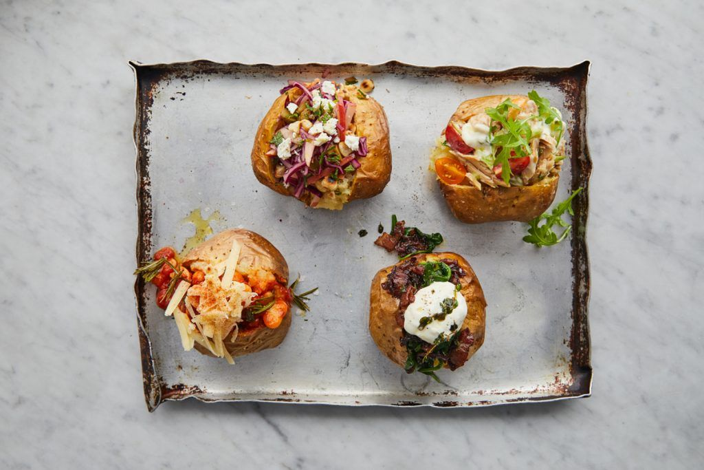 Jacket potatoes laid out on a baking tray