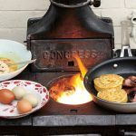 breakfast recipe - eggs, bacon and crumpets fried on a wooden fire