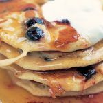 a stack of blueberry pancakes with cream and butter on top