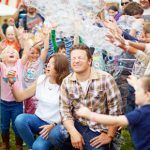 jamie and jools at a festival for food with kids surrounding them and bubbles