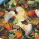 white fish soup with vegetables and herbs