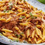 penne pasta with meat in tomato sauce and herbs