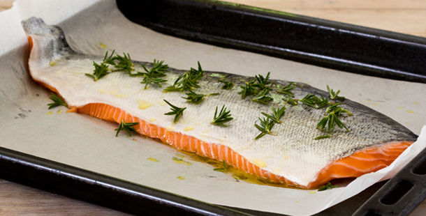 Salmon recipes - slice of raw salmon with herbs and oil on top