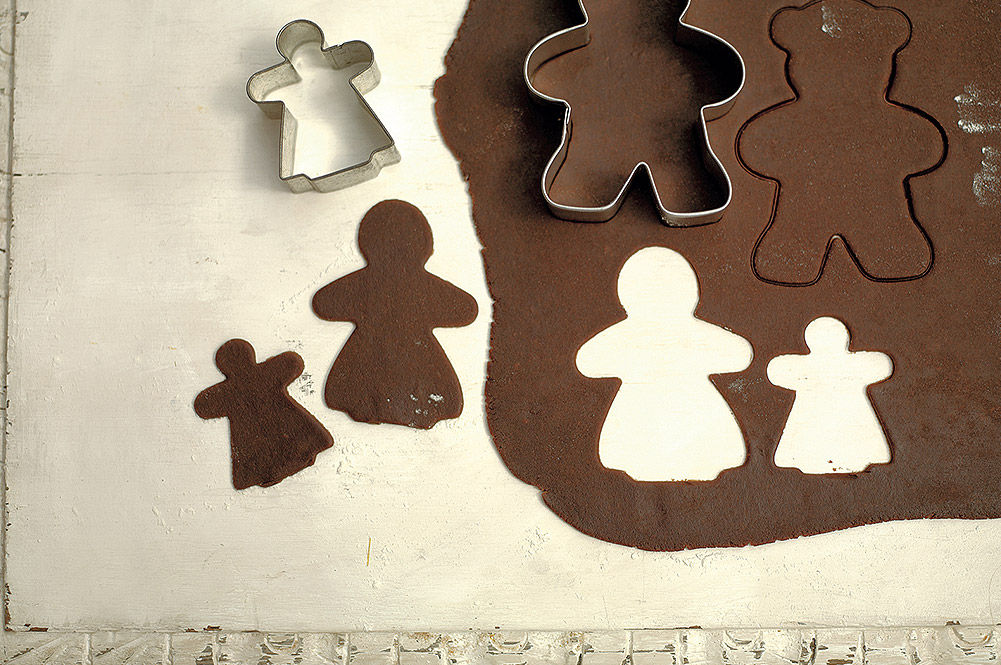 christmas gingerbread being cut out of dough