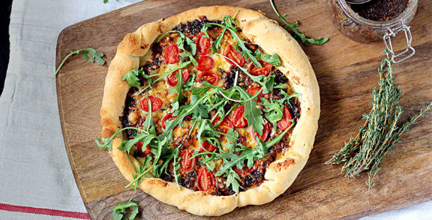 pizza recipe with tomato and herbs on top
