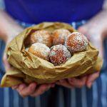 vegan doughnuts covered in sugar in a paper bag