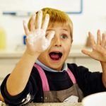 kid with flour on hand
