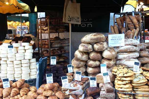 market with stacks of fresh breads, pastries and bakes