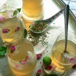 iced tea with alcohol added and rose buds in the drinks