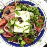 greek cheese with salad and herbs on top with olives