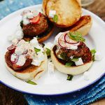 lamb sliders on top of a bread bun with sour cream and feta