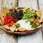 perfect nachos with herbs, guacamole, chilli, sour cream and refried beans