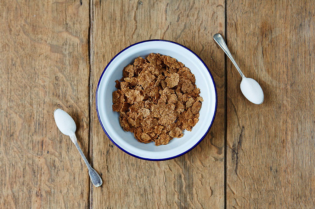 bran flakes cereal with 2 spoons of sugar next to it