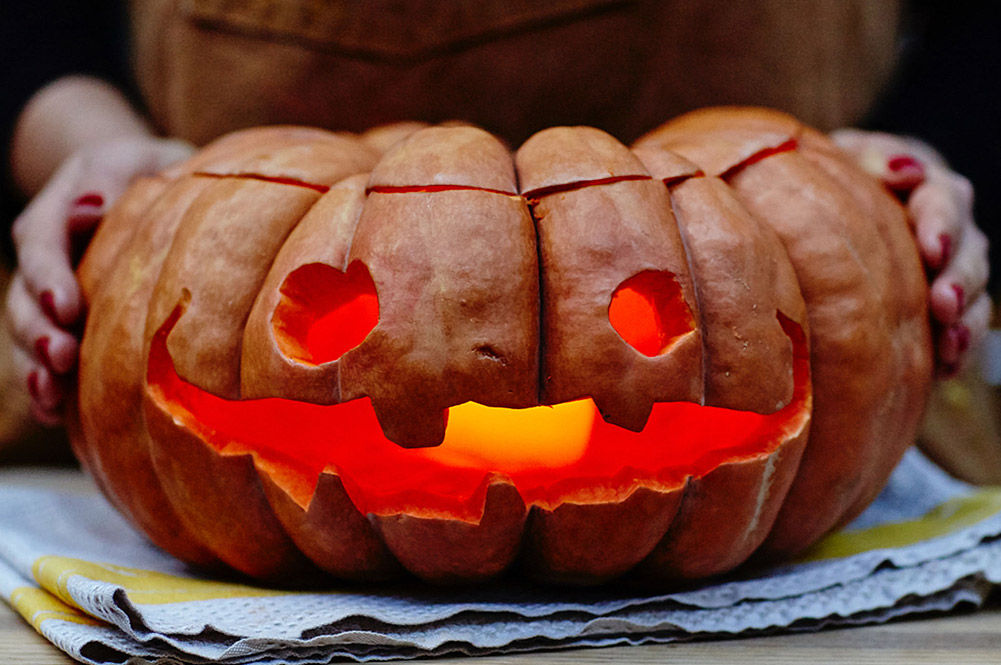 carve a pumpkin with candle in mouth