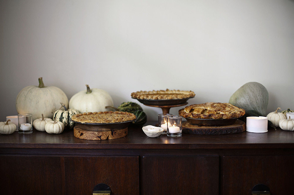 thanksgiving display with pies surrounded by pumpkins and squash