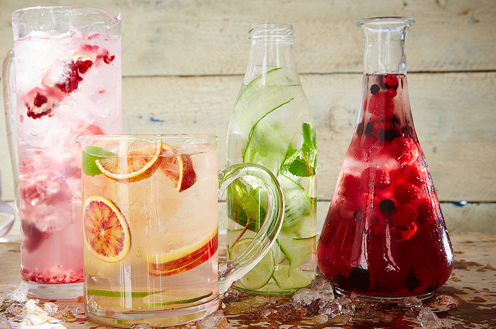 jugs of water with fruit infused in them and ice