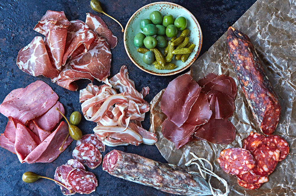 british charcuterie - a spread of different hams with olives and gherkins