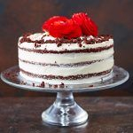 red velvet cake on a stand with roses on top