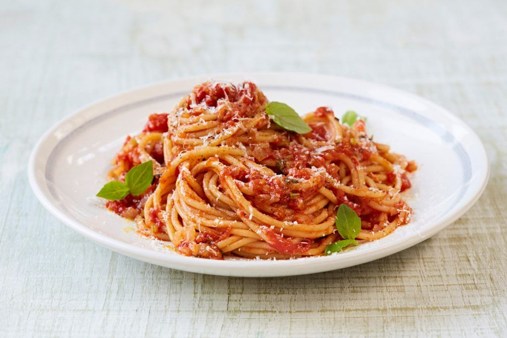 tomato spaghetti on a plate with basil on top