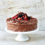chocolate cake with berries on top and on a cake stand with chocolate shavings