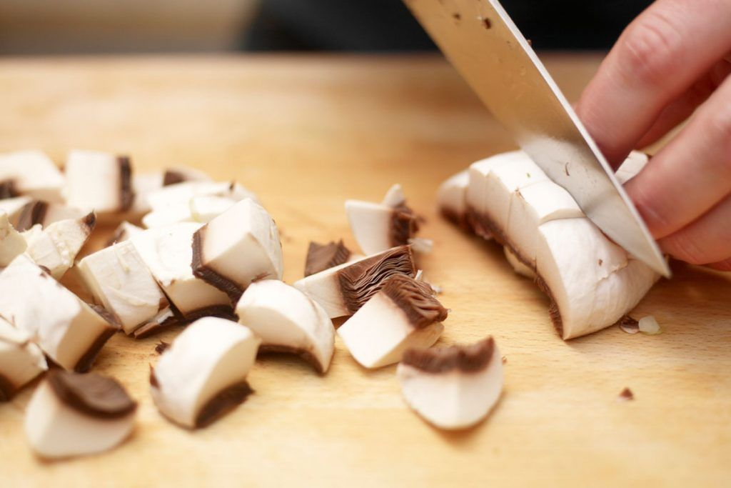 mushrooms being sliced on a chopping board