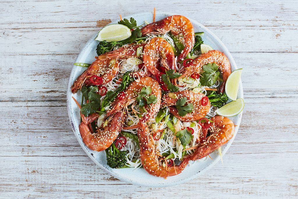prawns covered in sesame seeds in a noodle spring onion salad and slices of lime