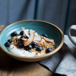 granola, oats, coconut shavings, blueberries and yoghurt in a bowl with lemon tea on the side