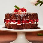 perfect chocolate cake with raspberries, strawberries and cream on top