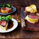 beef wellington recipe on board sliced in sections with gravy and broccoli