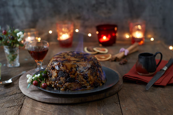 christmas pudding with drinks and candles around