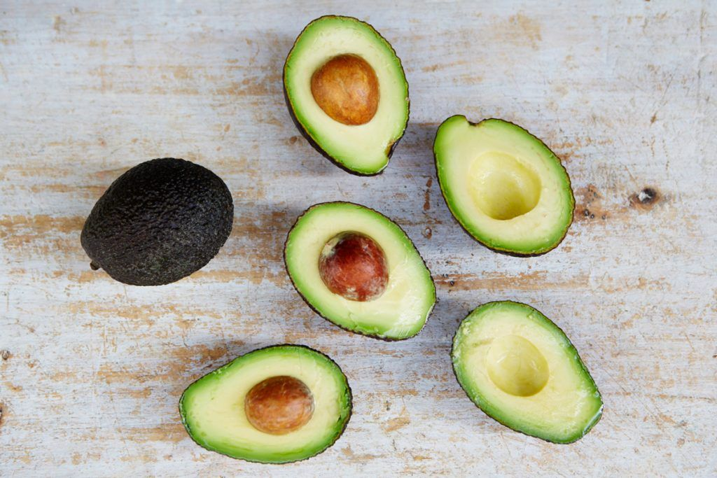 a scatter of avocados cut in half