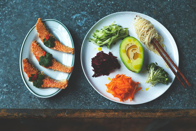asian dish with sesame seed fish and a plate of veg, noodles and avocado
