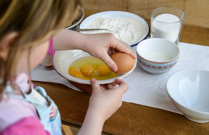 Image of a child cracking eggs into a bowl