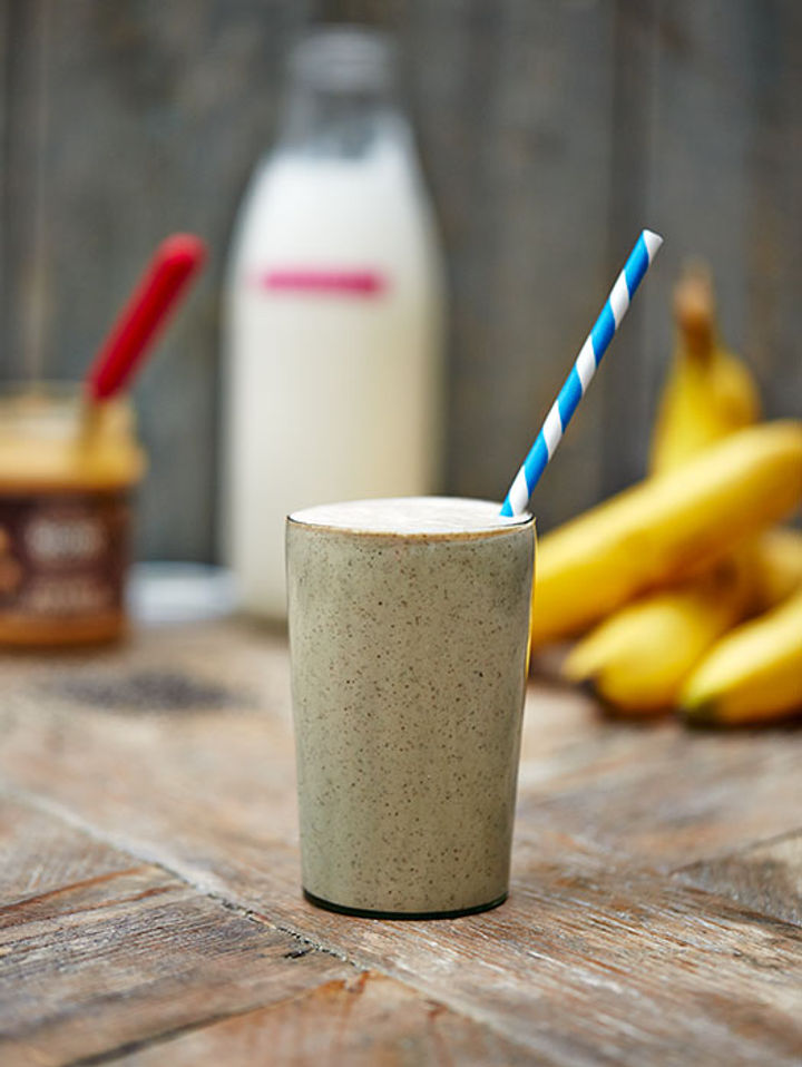 Image of a glass full of protein shake with a blue and while straw