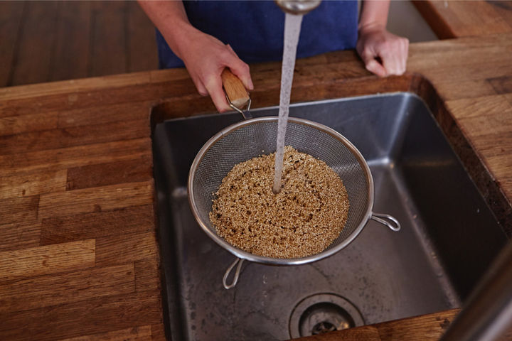 Image of a sieve of quinoa being rinsed in a sink
