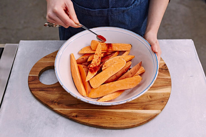 Image of raw sweet potato wedges being coated with spices